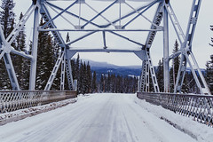 Winter scene of a bridge crossing the Bow River on the snow covered, icy Bow Valley Parkway in Banff National Park Canada (m01229) Tags: bowvalleyparkway bridge peaceful nature frost trestlebridge destination snow banffnationalpark national road banff canada bowvalley canadianrockies valley landscape winter rocky mountains outdoor travel clouds calm rockies scenic alberta canadian adventure scenery beautiful highway forest bowriver river panoramic park trees tourism wilderness mountain