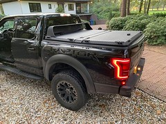 A Heavy Duty Truck Bed Cover On A Ford Raptor (DiamondBack Truck Covers) Tags: aluminum tonneaucover truckbedcover diamondback diamondplate pickuptruck blacktruck ruggedblack hd heavydutytruckbedcover ff15 c ford f150 raptor closed lowprofilecabguard cg driversidetaillightview driveway