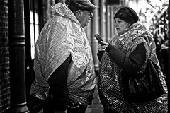 He Spotted It, She Checked It (garryknight) Tags: sony a6000 on1photoraw2018 london themonoseries monochrome blackandwhite copyright allrightsreserved wet rainy raining raincoat spots check tourist man woman couple coventgarden market rainmac