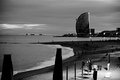 You look beautiful in black (Fnikos) Tags: sea water bay seascape landscape waterfront coast beach shore seashore sand sidewalk light reflection sky skyline city architecture building tower skyscraper dark darkness people night nightview nightshot blackandwhite monochrome outdoor