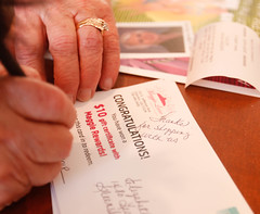 Elaine Vickery, 73, assistant manager of Maggie Lane, from Commerce, Georgia, fills out a coupon card to send to frequent customers. She says the shoppers are very excited to recieve these in the mail, and it often brings them back to the store to shop.