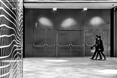wall decor (heinzkren) Tags: schwarzweis blackandwhite bw sw monochrome urban candid couple design indoor center shopping mall shoppingmall lights lines street dekor streetphotography people canon powershot exit ausgang tür door