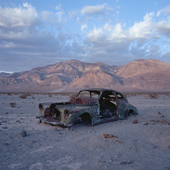 long term parking. panamint valley, ca. 2018. (eyetwist) Tags: eyetwistkevinballuff eyetwist abandoned car rusty panamintvalley deathvalley mojavedesert desert california mamiya 6mf kodak ektar 100 mamiya6mf kodakektar100 50mm mamiya50mmf4l ishootfilm ishootkodak analog analogue film emulsion mamiya6 square 6x6 mediumformat 120 filmexif iconla lenstagger epsonv750pro highdesert decay rust arid dry desolate mountains history mountain sky panamint landscape sunset vintage bulletholes auto coupe mojave dvnp death valley