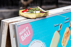 Durian gelato (A Different Perspective) Tags: bali advertisement banana blue incense leaf offering pink poster stand stext