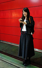 Talking by the Red Wall - Shibuya, Tokyo, Japan (TravelsWithDan) Tags: woman redwall candid street shibuya tokyo japan night talking phone sweater longskirt