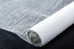 White bandage on black background (wuestenigel) Tags: protection treatment gauze doctor emergency help fix assistance aid adhesive bandage pain medical first care skin medicine patient health injury recovery cure wound white noperson keineperson desktop cotton baumwolle texture textur fabric stoff closeup nahansicht wear tragen industry industrie stilllife stillleben abstract abstrakt yarn garn roll rollen pattern muster textile textil one ein color farbe fashion mode
