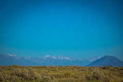 A look across the pampas at the snow capped Andes mountains with a volcano in the foreground.