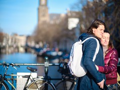 Wintersun and Love (claudia 222) Tags: people sun winter amsterdam canal gracht candid women man water sky astia fuji love zeiss zeissplanart85mmf14zf2 manualfocus bycicle embrace bokeh bridge