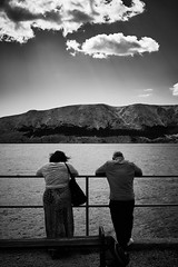 Staring at the sea (iamunclefester) Tags: vacation holiday croatia krk otokkrk blackandwhite monochrome sea water couple baška balustrade handrail outlook lookout bella vista clouds cloud street mountains mountain lightray ray rayoflight waiting bench staring