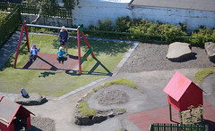 Swinging In The Sun (peterkelly) Tags: digital canon 6d europe iceland reykjavik gadventures bestoficeland hallgrimskirkja view neighbourhood city playground swings swingset children child mother hat boulder sand wall tireswing tire park tower