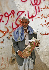 Qat Seller Holding A Bag Of Qat, Seiyun, Yemen (Eric Lafforgue) Tags: adult arabia arabiafelix arabianpeninsula beard colourpicture day greyhair handholding housing man oldman oneperson package placeofinterest realpeople salesman salesperson vertical wall wisdom yemen 01004yemenlafforgue seiyun