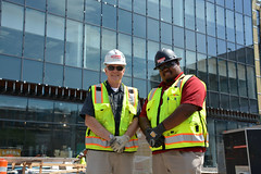 """Alumni Joe Callaghan, BCS '76, and Obadiah """"Obie"""" Rankin, BSCM '14, pose in front of the Center for Engineering, Innovation, and Sciences on a late July day. Callaghan was the Senior General Superintendent for the project and Rankin was a project engineer (Wentworth Institute of Technology) Tags: bag clothing computerhardware fireman hardhat helmet human people person vest"""