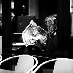 Reading the news (pascalcolin1) Tags: paris13 femme woman nuit night café table chaises chairs journal newspaper lisant reader reading photoderue streetview urbanarte noiretblanc blackandwhite photopascalcolin 50mm canon50mm canon lumière light vitre window