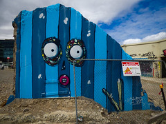 He's Wearing Pinstripes (Steve Taylor (Photography)) Tags: stripes face eyes donotenter danger cactus jacobryan yikes cartoon graffiti mural streetart sign fence chainlink blue brown rubble concrete newzealand nz southisland canterbury christchurch cbd city sky cloud