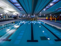The Pool Perspective (Steve Taylor (Photography)) Tags: architecture light window blue black mauve red yellow calm water newzealand nz southisland canterbury christchurch northnewbrighton perspective reflection lines twilight dusk pool rubberring swimmingpool taioraqeiirecreationandsportcentre