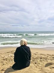 Back in Black (ijp01) Tags: spain barcelona catalonia platjadelabarceloneta beach sand woman blonde sweater black waves breakers coastline horizon portrait glance shadow clouds overcast mediterraneansea balearicsea alone contemplation shimmer glow