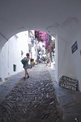 La sirena. (elojeador) Tags: mujer chica sirena joven calle arco piedra acera pueblo cadaqués balcón buganvilla paseo turista cable arbusto planta restaurant elojeador