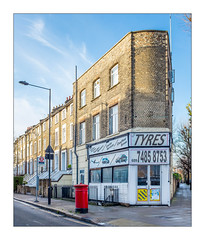 The Built Environment, Tyre Shop, North London, England. (Joseph O'Malley64) Tags: thebuiltenvironment newtopography newtopographics manmadeenvironment manmadestructures building structure victorianbuildings victorian disappearinglondon urban urbanlandscape architecture architecturalphotography britishdocumentaryphotography documentaryphotography shop shopfront tyreshop frontage corner cornershop brickwork bricksmortar cement pointing render battenmouldings homes houses dwellings abodes townhouses basements walls windows repairs alterations drainpipes busstop streetlighting streetlamp lighting signs sighnage railings ornamentalironwork ironwork castironrailings postbox victorianpostbox tvaerial redundantanaloguetvaerial pavement granitekerbing ramp tactilepavingforthevisuallyimpaired draincovers doubleyellowlines noparkingatanytime parkingrestrictions tyres cartyres fujix fujix100t accuracyprecision londonplanetrees
