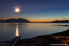 Sunset + Moonset (james c. (vancouver bc)) Tags: sky star reflection reflect rock driftwood peaceful tranquility tranquil abstract background beautiful beauty blue cloud contour dark dusk evening glow heavenly sea ocean beach landscape light moon moonset mountain island longexposure smooth nature orange outdoor planetarium scenic winter autumn fall moonlight sunset twilight view yellow silhouette radiance