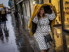 Spotting with Rain (Leanne Boulton) Tags: urban street candid portrait portraiture streetphotography candidstreetphotography eyecontact candideyecontact streetportrait candidstreetportrait colourstreetphotography streetlife woman female face eyes expression mood feeling atmosphere rain raining winter weather yellow coat spotty spots dress fashion style dutchangle blue wet reflection tone texture detail depthoffield bokeh naturallight outdoor light shade city scene human life living humanity society culture lifestyle people canon canon5dmkiii 40mm ef40mmf28stm color colour glasgow scotland uk leanneboulton