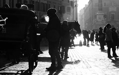 Backlight in Piazza di Spagna (lucafabbricesena) Tags: backlight roma piazzadispagna italy rome people streetphotography contrast blackandwhite bw horse gig smoke knigth cigarette nikon d800 nikkor morning sunlight winter city square