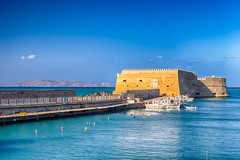 Koules Fortress and Old Venetian Harbour with Lines of Sailing Fishing Boats At Noon in Heraklion City, Greece. (DmitryMorgan) Tags: quay aegean bay blue boat building capital city cityscape coast coastal cretan crete dawn europe european evening fort greece greek harbor harbour hellenic heraklion historical iraklio iraklion island koules landmark lights mare marina maritime mediterranean motorboat nautical old picturesque pier port sea ship shipyards summer sunset tourism travel traveling venetian vessel view water wharf yacht
