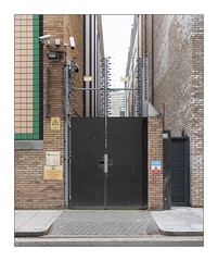 The Built Environment, East London, England. (Joseph O'Malley64) Tags: thebuiltenvironment newtopography newtopographics manmadeenvironment manmadestructures urbanlandscape industriallandscape industrialestate alley alleyway yard gates yardgates steelgates fortifiedsecurity secured nationalgrid electricity dangerofelectrocution dangerofdeath hazard architecture architecturalphotography architecturalfeatures britishdocumentaryphotography documentaryphotography eastlondon eastend london england uk britain british greatbritain steelreinforcedconcretestructures brickworkcladding brickwork bricksmortar cement pointing pier electricfence deterrent tiling steeluprights wiring electricalwiring cctv cctvcameras securitycameras monitoring lamp spotlamp lighting signs signage louvres vents transformers powertranformers powersupply concrete pavement blockpaving ramp entrance exit granitekerbing tarmac doubleyellowlines noparkingatanytime parkingrestrictions instarmacrepair urban accuracyprecision