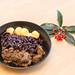 Rindergulasch nach traditioneller Art mit Apfelrotkohl und Miniknödel mit einem Zweig auf einem Holztisch