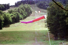71-095 (ndpa / s. lundeen, archivist) Tags: nick dewolf nickdewolf color photographbynickdewolf 1975 1970s film 35mm 71 reel71 hanggliding hangglidingfestival damagednegative tear torn ripped negative hill mountain skirun lift skilift chairlift hangglider hanggliders windsock grass trees franconia franconianotch newhampshire newengland mittersillalpineresort mittersill cannonmountain whitemountains worldcup competition hangglidingcompetition summer worldcupmeet meet mittersillworldcupmeet july