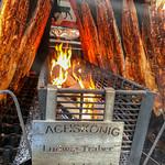 Flammlachs vom Lachskönig gart auf Metallspießen über offenem Feuer thumbnail