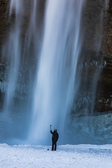 Selfie-taker at Seljalandsfoss Waterfall in Iceland (Lee Rentz) Tags: eyjafjallajökull iceland ringroad route1 seljalandsfoss seljalandsá southcoast adventure beautiful behavior cascade cold down experience falling frigid geopark glacial glacier ice icy landscape man march nature outdoors path picturesque river scenic selfie selfiestick snow snowy spray stream streaming takingselfie tourism tourist trail travel traveler vertical walkway water waterfall wet winter wintry