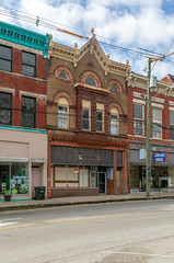 Building — Carlisle, Kentucky (Pythaglio) Tags: building structure carlisle kentucky unitedstatesofamerica us commercial historic ornate stone stonework romanesque storefront sidewalk street clouds nicholascounty rusticated roundarched 11windows finials ca1900