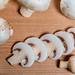 Fresh champignon mushrooms on wooden background.