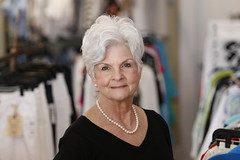 Merchant poses for a portrait in the boutique. Merchant has been the manager of this location for three years. She previously worked in education for 35 years before retiring.