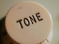 Anglų lietuvių žodynas. Žodis tone reiškia 1. n 1) tonas, garsas; deep/low tone žemas tonas; high/thin tone aukštas tonas; angry tonepiktas tonas; heart tones med. širdies tonas; 2) tonas, stilius, charakteris; 3) med. tonusas; 4) intonacija, moduliacija; atspalvis;2. v 1) duoti toną; 2) derinti ( lietuviškai.