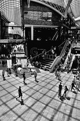 Square Dancing (tcees) Tags: cabotcircus southstreet bristol nikon d5200 1855mm bw mono monochrome blackandwhite uk urban streetphotography street man woman people shops roof ceiling shadows reflection escalator shopping shoppers dancing