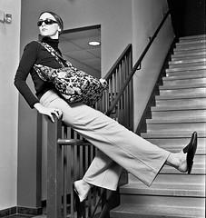 Megan 1 (neohypofilms) Tags: series retro fashion style fun 70s pants slacks shades glasses tall long legs flats mules slippers clogs girl model actress talent bw hasselblad blackandwhite 120 medium format film cinema concept conceptual art stairs steps shoes purse handbag