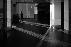 Interplay of Light and Shadow (明遊快) Tags: gr2 building man sunlight shadows urban lines contrast monochrome dusk kyoto bw people candid
