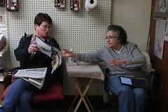 Burden (left) and Brook (left) discuss a magazine.