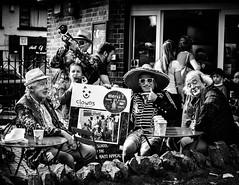 Jester gesture (Kieron Ellis) Tags: people man men girl sitting clowns trumpet table chairs sign cafe coffee hat sombrero sunglasses harmonica candid street blackandwhite blackwhite monochrome
