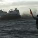 Seaman guides a landing craft air cushion to shore.
