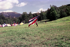 71-066 (ndpa / s. lundeen, archivist) Tags: nick dewolf nickdewolf color photographbynickdewolf 1975 1970s film 35mm 71 reel71 hanggliding hangglidingfestival hills mountains sky bluesky clouds tree grass hillside landing hanggliders parked franconia franconianotch newhampshire newengland mittersillalpineresort mittersill cannonmountain whitemountains worldcup competition hangglidingcompetition summer worldcupmeet meet mittersillworldcupmeet july
