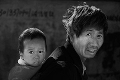 man carrying child (trying to catch up again !!!) Tags: man china child chineseman bw blackandwhite streetphotography streetlife backlight travel outdoor outside portrait candid ivodedecker
