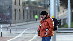 Waiting for the tram (Frank Fullard) Tags: frankfullard fullard candid street portrait passenger wait train tram transport red dublin luas irish ireland backpack cap beanie hat colour color rails