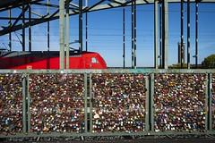 Locks and trains ... seen in Cologne, Germany (Martin Bärtges) Tags: nordrheinwestfalen strassenfotografie streetphotography stadt cityscapes köln city blau himmel blue sky red lokomotive zug sonne sonnenschein sunshine sun autumn herbst farbenfroh drausen outdoor outside colorful nikonphotography nikonfotografie d4 nikon cologne trains keylock schlösser schlos locks