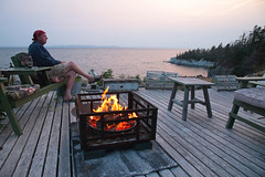 Deck Moment (peterkelly) Tags: digital canon 6d northamerica canada newfoundlandlabrador cavendish deck man table chairs chair bandana sunset evening dusk whitepoint trinitybay water fire flames lit heat hot wooden wood lobstertrap sitting