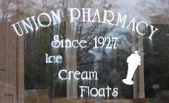 A sign painted on one of the front windows of Union Pharmacy.