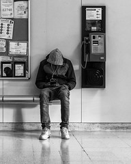 Head Down (Sam Codrington) Tags: reflection youth sitting shadow spring monochrome mono bench people birmingham texting birminghaminternationalstation hoodie blackandwhite streetphotography telephone england unitedkingdom gb