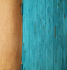 Tattered Turquoise (studioferullo) Tags: abstract architecture art beauty bright building colorful colourful colors colours contrast dark design detail downtown edge light lines minimalism perspective pattern pretty study texture tone world turquoise blue adobe paint wood wall harwood museum taos newmexico