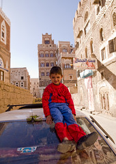 Smiling Kid Wearing A Spiderman Suit And Adult Shoes, Sitting On The Top Of A Car, Sanaa, Yemen (Eric Lafforgue) Tags: arabesque arabia arabiafelix arabianpeninsula architectural architecture blue bluesky boy building car child colourpicture day fulllength historical history housing innocence interesting lookingatcamera oldcity oldpeople oneboy oneperson placeofinterest realpeople sana sanaa sit sitting sittingposition smile smiling spideman street sun vertical yemen youth a0701276
